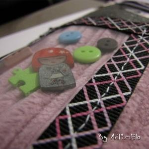Trousse en velours rose et tissu imprimé rose et gris, agrémentée de rubans et de petits éléments mobiles dans une vitrine en plastique.